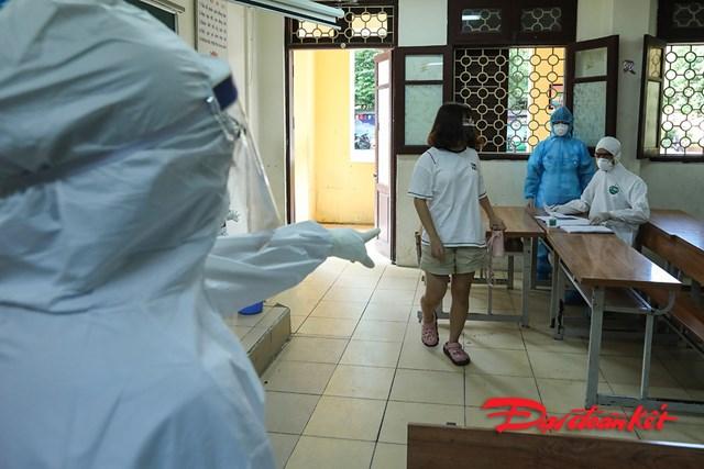 Cán bộ y tế hướng dẫn người đến làm xét nghiệm các thủ tục xét nghiệm.