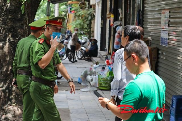 Công an phường Hàng Mã nhắc nhở người dân tham gia giao thông và những hàng quán vỉa hè thực hiện đeo khẩu trang theo quy định.