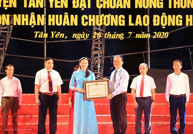 Bà Dương Tuyết Lan - Trưởng ban Dân vận, Chủ tịch Ủy ban MTTQ huyện Tân Yên đón nhận Bằng khen của UBND tỉnh tặng đơn vị có nhiều đóng góp trong xây dựng NTM tại Lễ công bố huyện Tân Yên đạt chuẩn NTM.